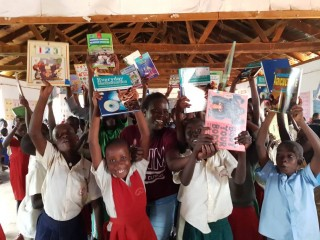 Students of Bukasa Primary School holding a donation of books from Kitabu-Buk Project
